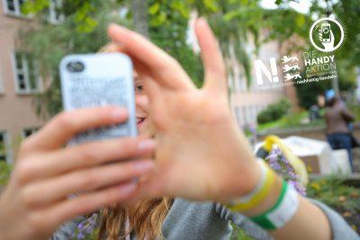 Junge Frau macht mit Smartphone ein Foto