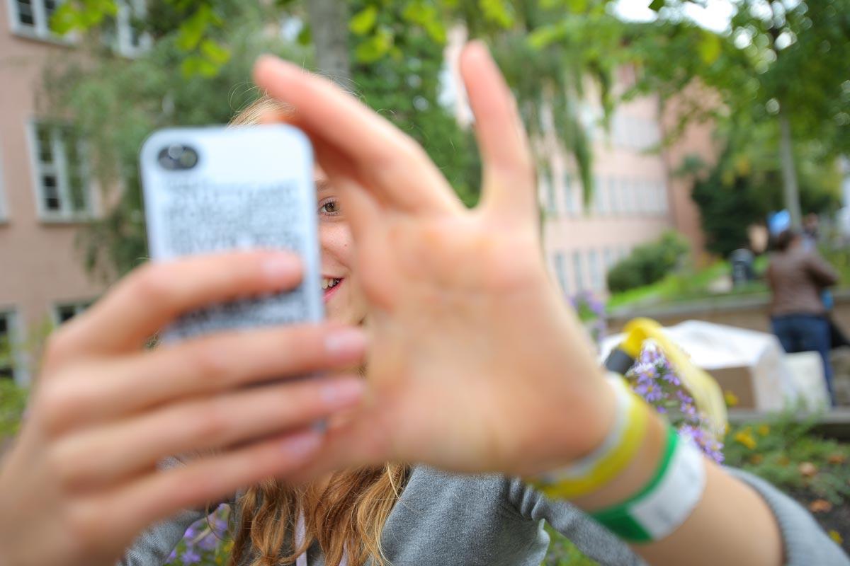Junge Frau mit Smartphone macht ein Foto