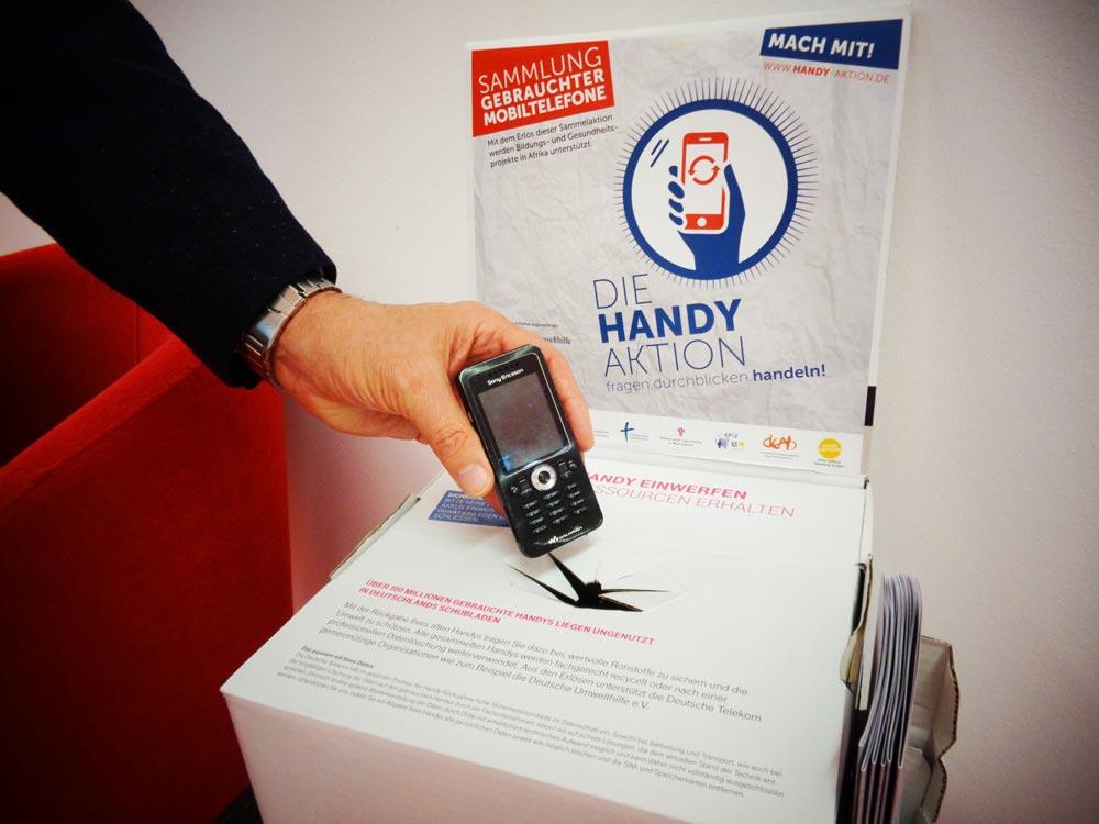Handysammelbox der Handy-Aktion Bayern – Einwurf eines Alt-Handys Smartphone für die Handy-Sammelaktion