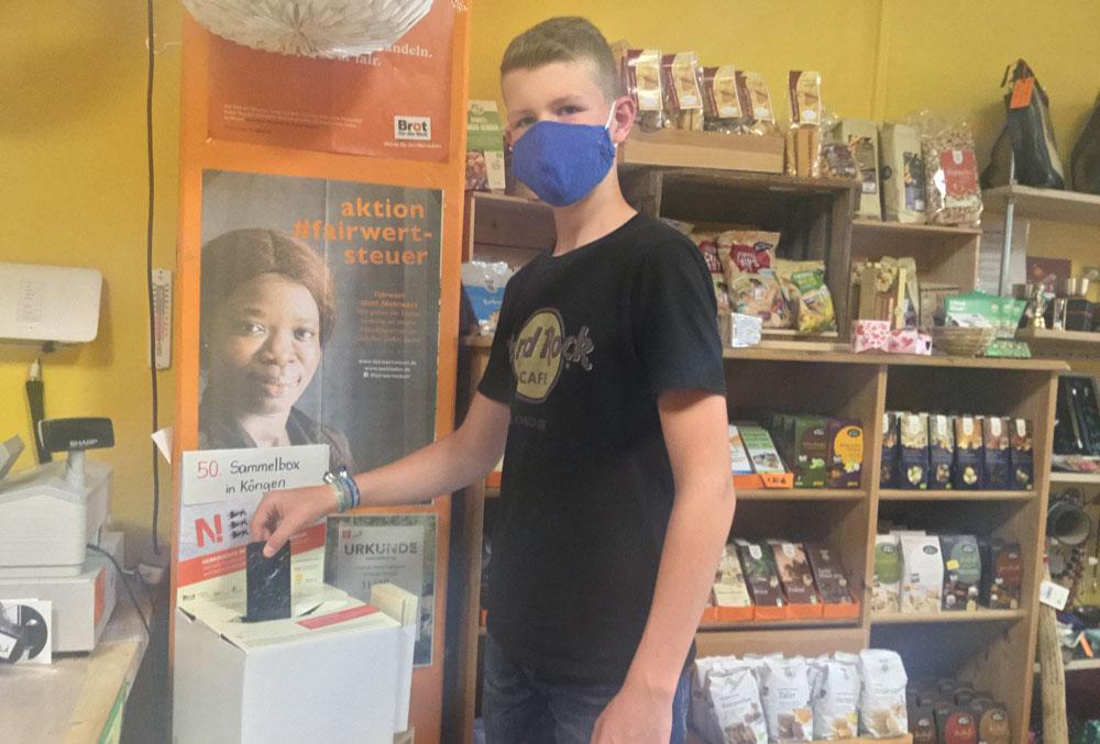 Junger Schüler mit Mund-Nase-Schutzmaske steckt gebrauchtes Handy in die Handysammelbox der Handy-Aktion Baden-Württemberg